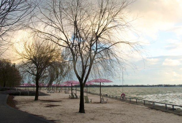 Sugar beach with its white chairs and pink umbrellas, looking over the sand towards Lake Ontario