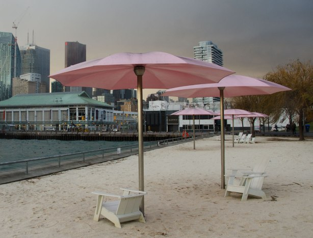 Sugar beach with its white chairs and pink umbrellas is in the foreground and the city is behind it.