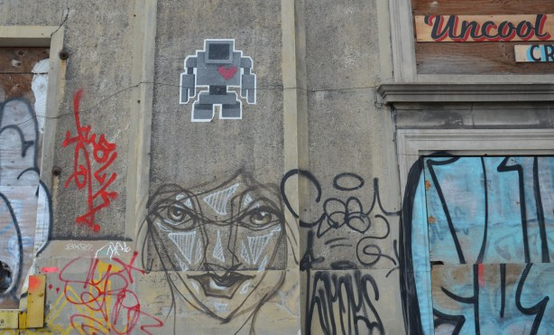 lovebot and an anser black, white and grey face on a conrete wall.