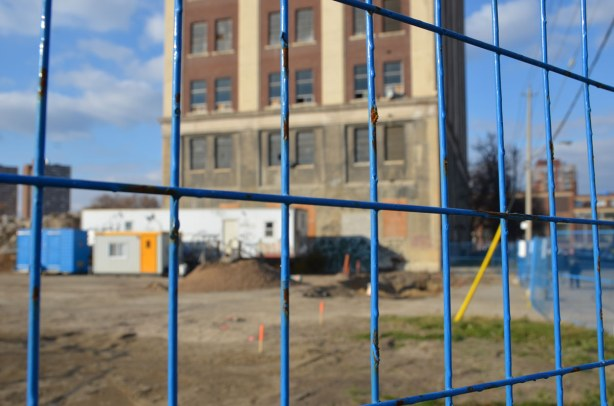 blue construction fence is in focus in the foreground with a construction site behind it.  A tall brick building stands in the construction site.