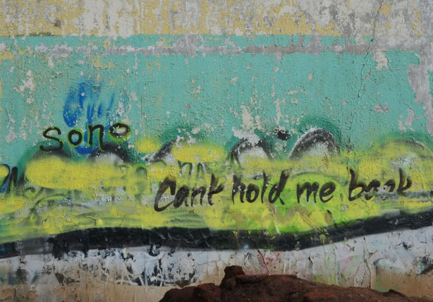 graffiti on the back of the Tower Automotive building, a tall brick building - the words cant hold me back are written in black on top of yellow and turquoise.