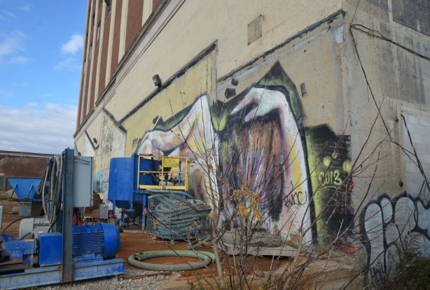 graffiti on the back of the Tower Automotive building, a tall brick building - looking along the side of the building, the head of the reclining woman is in the foreground.  Construction equipment is also in the picture.
