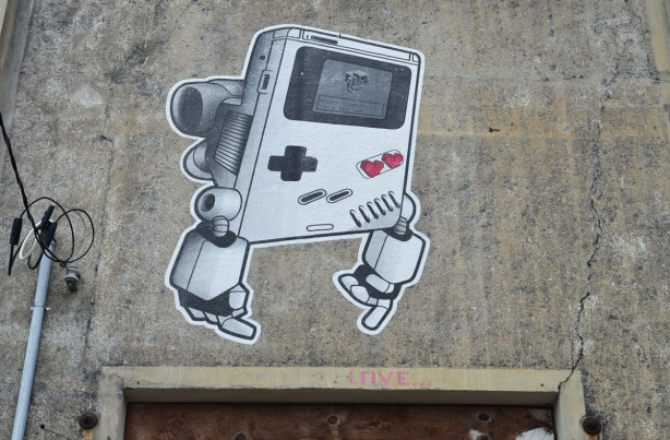 a large gameboy lovebot on the side of a concrete wall.