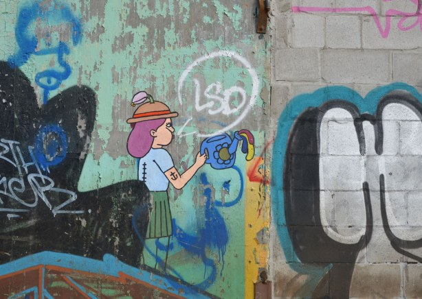 graffiti on the back of the Tower Automotive building, a tall brick building - a woman with purple hair wearing a brown and red hat.  She is holding a blue watering can.  She has an anchor tattoo on her upper arm.