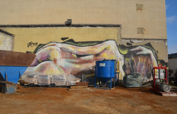 graffiti on the back of the Tower Automotive building, a tall brick building - the backside of a naked woman who is lying on the ground.  Much larger than lifesize, painted by Jarus.