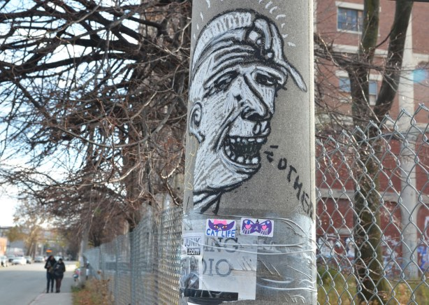 On a concrete telephone pole, a black and white drawing of a man's head.  The word Others is coming out of his mouth.