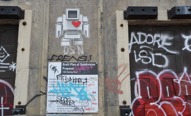 wall of a building with a wheatpaste lovebot and a standard city of Toronto development proposal sign.  Some tags are also on the building.
