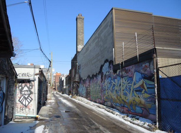 looking north up an alley.  On the right side is a large 3 storey building that has graffiti along the lower part of it.  On the left are garages with graffiti on them.