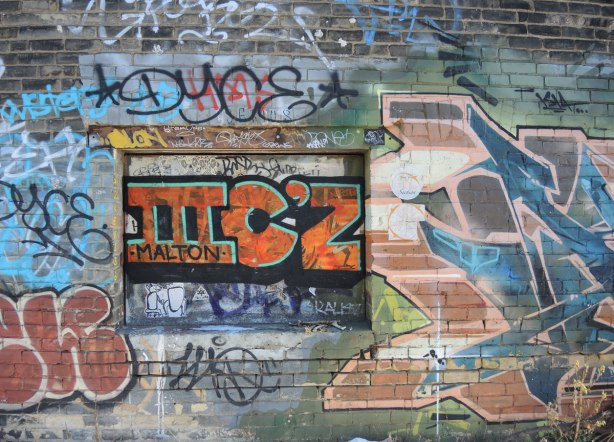 graffiti on a wall - a chaos of tags and colours on a brick wall