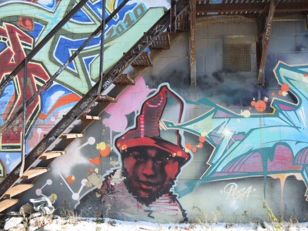 graffiti on a wall - a man with a red face and hat, painted under a metal staircase.
