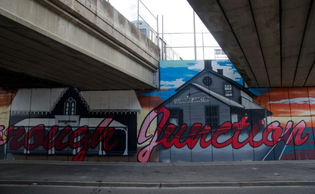part of mural under subway bridge, large red cursive letters that say Scarborough Junction.  A picture of an old Scarborough post office as well as a wood building that was a general store.