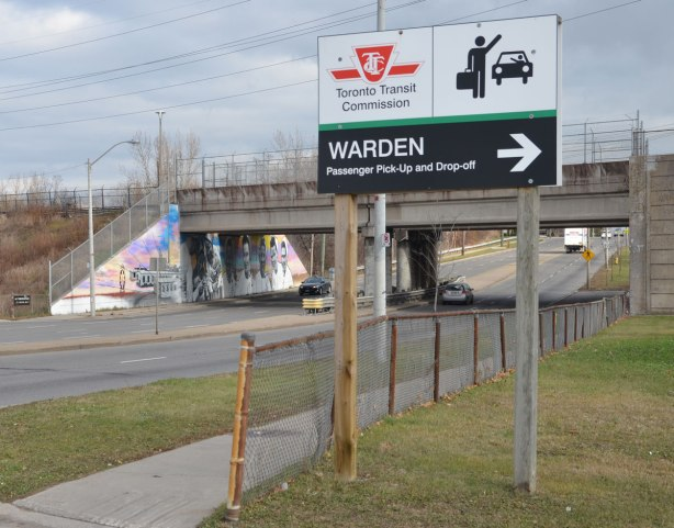 Beside a four lane road, a sign pointing to Warden station passenger drop off.  In the background is a bridge over the road.