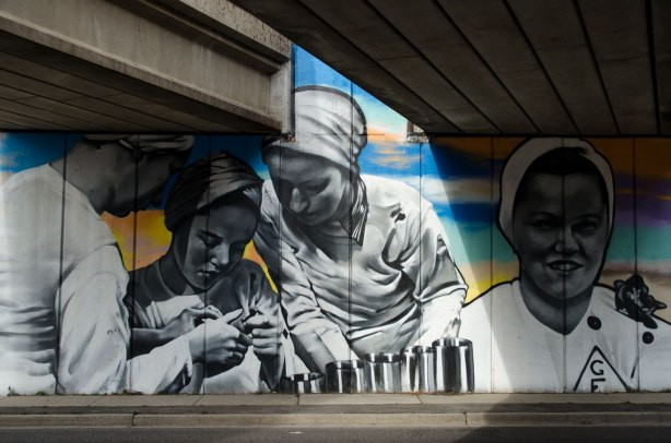 mural under subway bridge, showing woman munitions workers from the era of world war 2.  They are wearing white tops and white hair coverings.