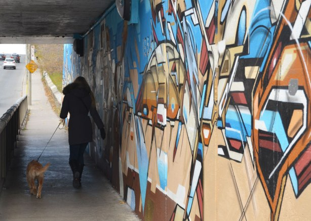 a woman walking her dog passes street art in blues and browns under a railway bridge