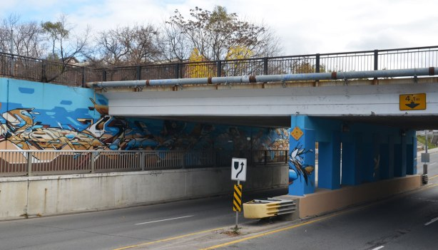 Street art in blues and browns under a railway bridge