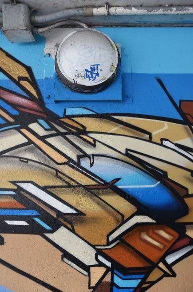 Street art in blues and browns under a railway bridge