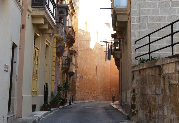 The sun shines from the end of an alley, limestone walls, laundry hanging from the balconies