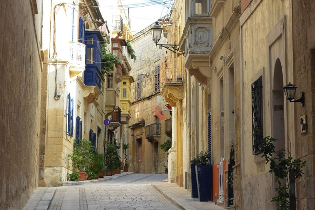 narrow street in Birgu, limestone buildings on both sides, colourful balconies overlooking the streets.