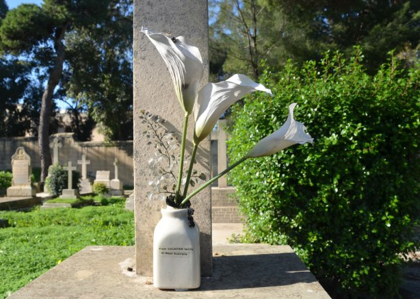 tombstone in a cemetery, with a vase of callia lilies in front of it.