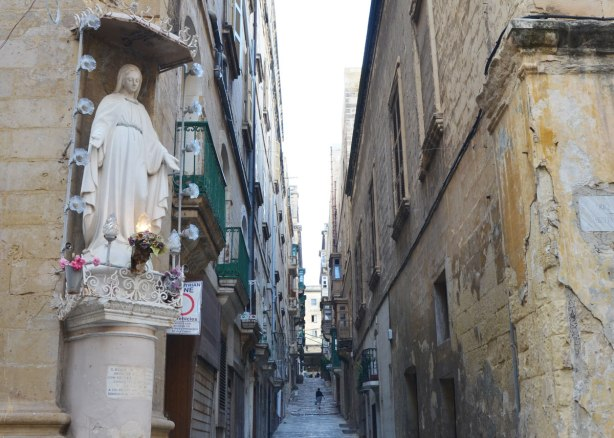 statue of a woman saint (Mary?) built into the corner of a limestone building in Malta