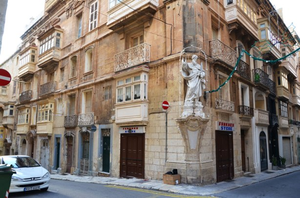 marble statue on the corner of a limestone building at the intersection in Valletta Malta.  Four storey building with balconies and a store on the corner by the statue