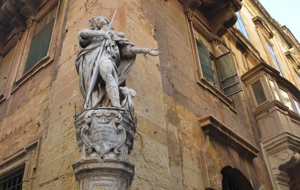 statue of a man built into the corner of a limestone building in Malta