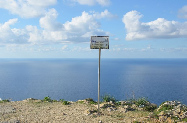 A small sign on a metal pole  in the edge of a cliff.  The Mediterranean Sea is behind, blue sky.  The sign says Do Not Litter Beyond the Cliffs.