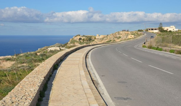 A two lane paved road that runs along the top of a small cliff at the edge of the sea.