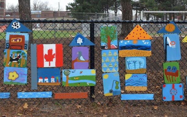 more of the collection of paintings by elementary school students that are hanging on a fence around the school.