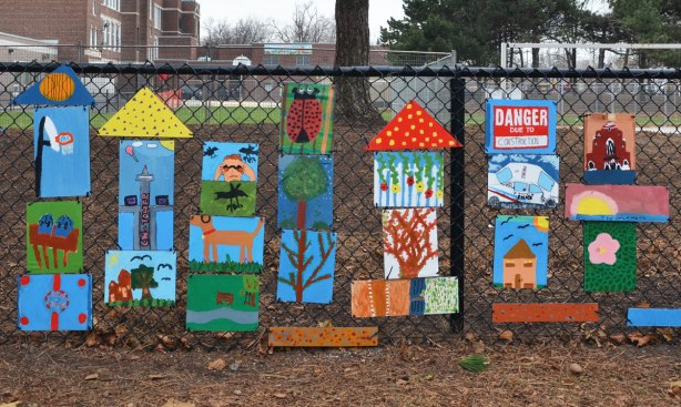 Close up of the fence at a school.  About twenty paintings done by the students.