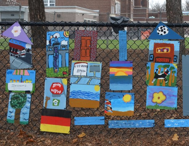 close up of the left part of the fence with paintings by students at the school.