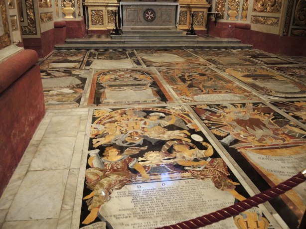 black, white, orange, gold tiles form memorials in the floor of St. Johns Co Cathedral in Valletta Malta.  There are numberous angels, skulls and skeleton motifs that cover almost every inch of the cathedral floor.