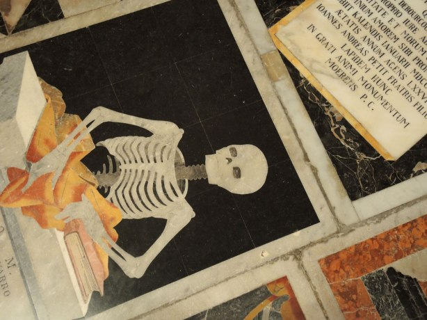 black, white, orange, gold tiles form memorials in the floor of St. Johns Co Cathedral in Valletta Malta.  There are numberous angels, skulls and skeleton motifs that cover almost every inch of the cathedral floor.  A skeleton is sitting at a desk and reading a book
