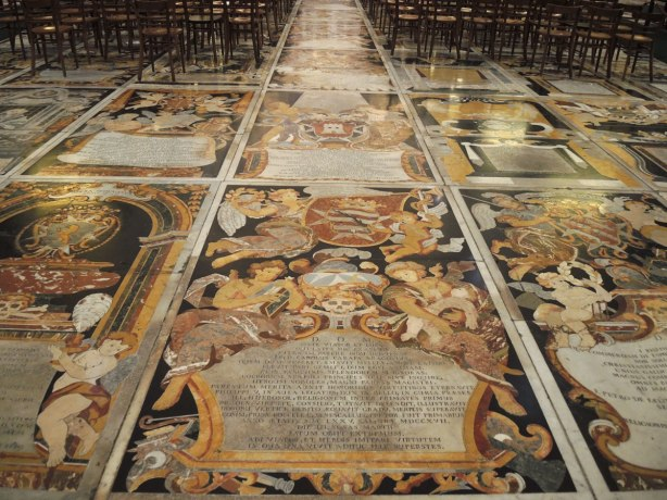 black, white, orange, gold tiles form memorials in the floor of St. Johns Co Cathedral in Valletta Malta.  There are numerous angels, skulls and skeleton motifs that cover almost every inch of the cathedral floor.
