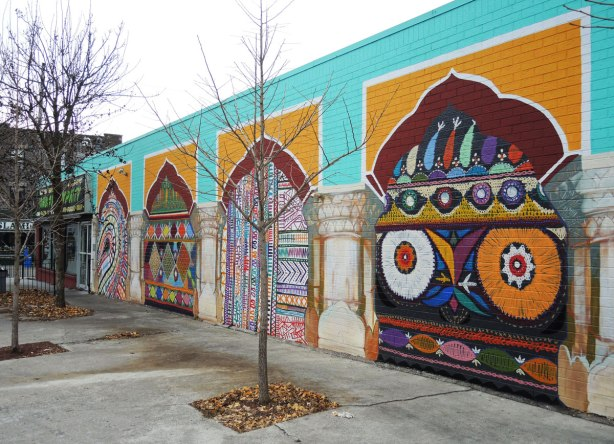 mural on the side of a one storey building showing 4 brightly coloured panels.  Turquoise in the background.  Each panel shows an archway between pillars.  Each of the 4 has a brightly coloured pattern