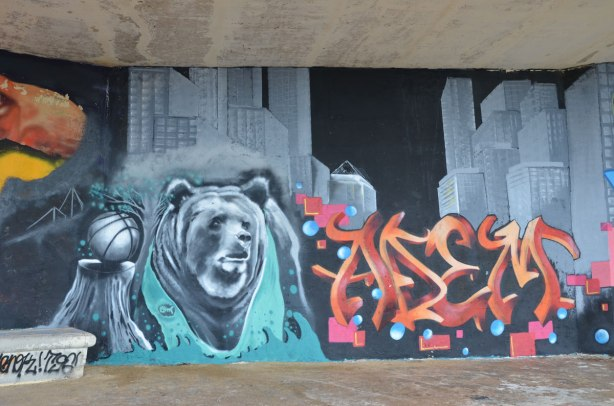 Graffiti picture of a basketball on a tree stump with a bear beside it.  Large skyscrapers are in the background.  A red and orange tag is also in the picture.