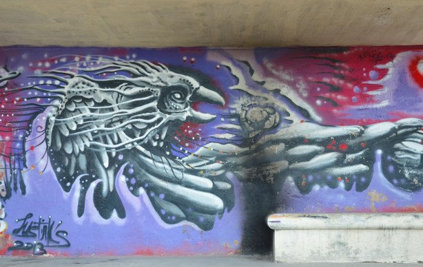 A large bird in grey tones flying on a purple background, graffiti on a wall.