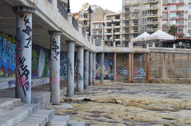 Sea wall with sidewalk above.  The sidewalk is supported by concrete pillars.  Rocks along the shore are in the foreground and the apartment buildings of Sliema are in the background.