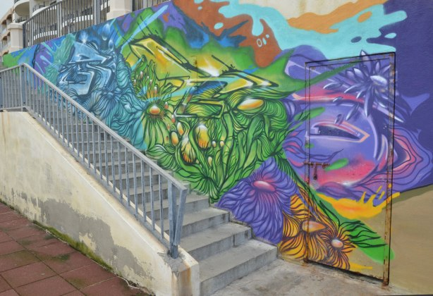 Colourful graffiti on a wall beside a set of stairs.