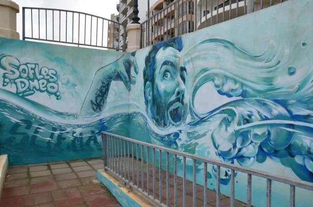 graffiti on a wall - a male swimmer amongst the waves, in shades of blue.