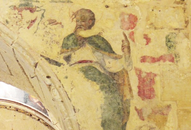 Close up of an old fresco on a wall, religious painting of a man holding onto a stone tablet that has words written on it