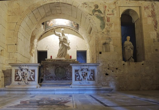 Inside a grotto, A statue in a niche in the wall on the right and another statue on an altar under an arch on the left