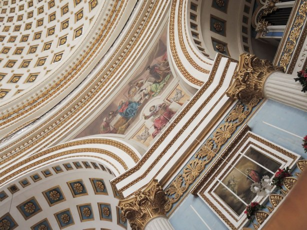 interior of a church showing a small part of the domed ceiling, part of two supporting arches and the picture that is painted in the space between the adjoining round arches.