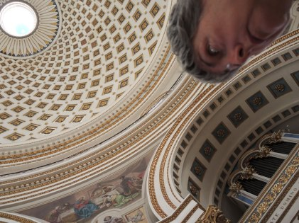 looking towards a large domed ceiling of a church with one of the rounded supporting arches in view.  part of my face is also in the photo.