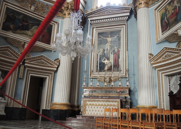 part of the inside of a church, chairs, blue walls, white pillars with gold tops, a large altar with 7 tall candles on it and a religious picture behind it.