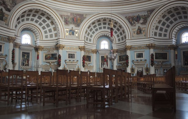 three of the arches supporting the Mosta Dome with chairs in the foreground