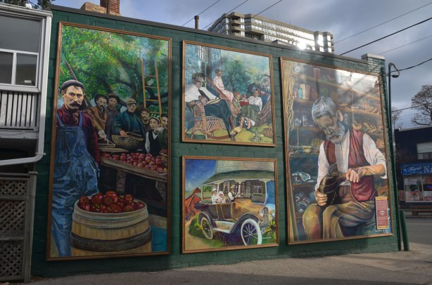 mural in 4 parts, 1 on the left, 1 on the right and 2 in the center.  The left depicts a man selling apples, the right depicts a cobbler fixing shoes.  In the center: bottom, a family in old fashioned car.  Center top - a family sitting in a livingroom including a man in a rocking chair