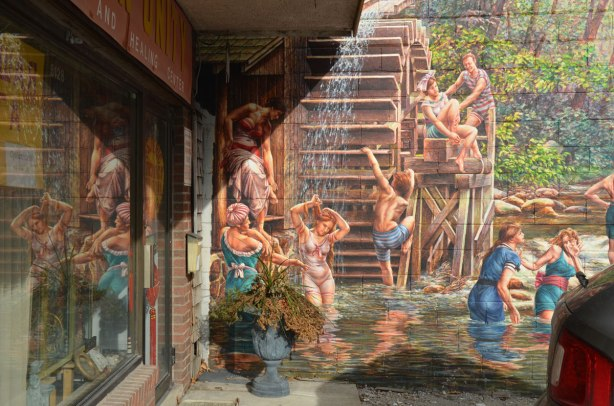 closer view of part of the mural of people swimming in a creek.  In this part of the picture, kids are climbing on a water wheel.  The mural is reflected in the window of the store next to it.
