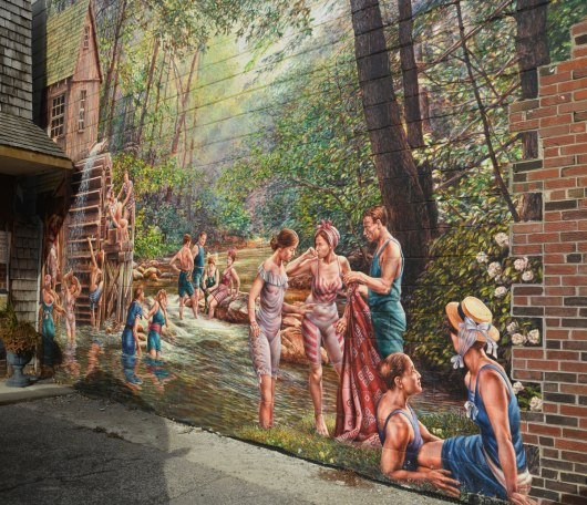 large mural of people swimming in a creek in bathing costumes from the 1920s