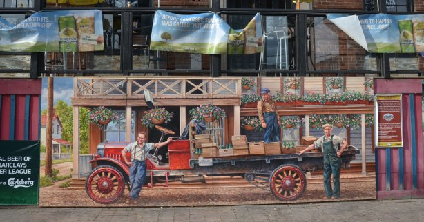 mural showing men loading an old flat bed truck with crates of empty pop bottles, 1920s